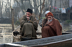 Kashmiri men try to keep warm in the bitter cold morning hours before sunrise as they sell their vegetables at a floating market on Dal Lake in the summer capital of Kashmir, Srinagar India, November 24, 2001. In the background, echoing through the nearby mountains, gunshots and fighting could be heard. Kashmir was once a tourist hotspot but now vendors struggle to survive in a place that has seen nearly 1000 civilians killed this year alone and 1,765 wounded in a brutal conflict that the United Nations calls the most dangerous place in the world.  (Photo by Ami Vitale/Getty Images)
