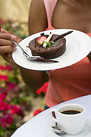 Woman eating dessert outdoors, mid-section