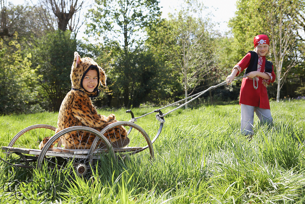 Young boy (7-9) in pirate costume pulling boy (5-6) in jaguar costume sitting on cart smiling