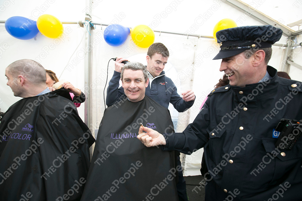 Clare's Tony Kelly about to shave the Head of Sargent  Mark Murphy as Sargent Paul Slattery donates a Euro  at  the Garda Shave or Dye event in O'Connell Square Ennis. .<br /> Pictured Credit Brian Gavin Press 22