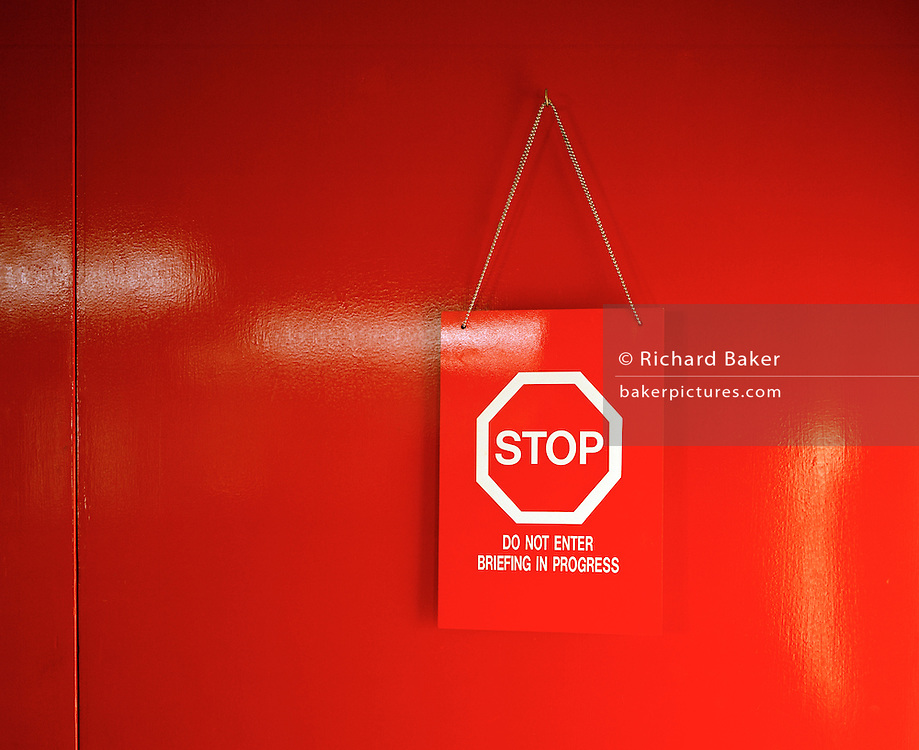 "A door painted with a high-gloss red finish is closed and a warning sign for privacy is hung to deter outsiders from entering. This briefing room belongs to the elite 'Red Arrows', Britain's prestigious Royal Air Force aerobatic team Lincolnshire, who use these offices as headquarters and administrative centre for the 90-plus displays they perform a year. The pilots' crew room is screened off from visitors and the notice says ""Stop, do not enter, briefing in progress"" to isolate the serious business of briefing and de-briefing. Performance appraisals before and after a training flight or air show displays are intense. Matters of safety and perfection are discussed so the aviators politely close the door unless visitors have been invited in to hear about the features of the next flight or afterwards, the gentlemanly exchanges providing analysis and frank views."