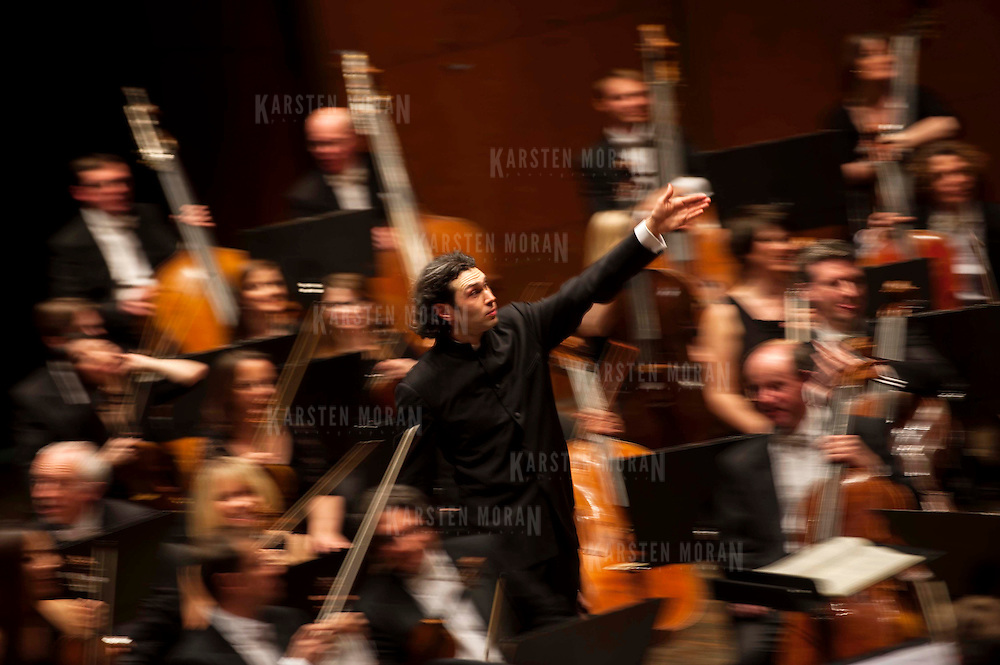 "March 11, 2013 - New York, NY : .Conductor Vladimir Jurowski, center, gestures toward the London Philharmonic Orchestra, as he acknowledges the audience's applause after a performance of Gustav Mahler's Symphony No. 5 in C-sharp minor (1901-02), part of Lincoln Center's ""Great Performers"" series at Avery Fisher Hall on Monday evening..CREDIT: Karsten Moran for The New York Times *The blurred/motion effect is created by using a slow shutter speed and panning the camera with the conductor.*"