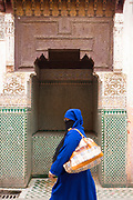 MARRAKESH, MOROCCO - 19TH APRIL 2016 - Eldery lady wearing traditional Moroccan clothing walks past the Zaouia / zawiya burial tomb shrine site of Sidi Ben Slimane - Shaykh Muhammad ibn Sulayman al-Jazuli, Marrakesh, Morocco. <br />