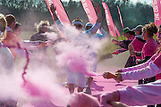 Two runners get sprayed with pink powder as they get closer to finishing the Color Run 5K. photo by Elizabeth Held