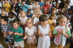 Multiracial group of infant school pupils clapping hands in assembly,
