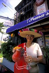 Stock photo of a woman wearing a sash and sombrero serving a red drink outside at Irma's Southwest Grill