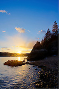 Idaho, North, Coeur d'Alene. Evening from the rocky shoreline of Tubbs Hill nature Park and Lake Coeur d'Alene at sunset.