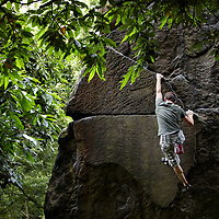 A photograph of a climber bouldering on grit stone at Caley Crags, near Otley, West Yorkshire, England