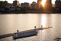 A cyclist sits on his bicycle with his child in back in a bike trailer on a dock over the Willamette river in Portland, Oregon.  Sunset