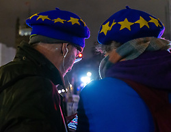 A couple watch the debate on their smartphone in Parliament Square as politicians debate Prime Minister Theresa May's Brexit deal in the House of Commons across the street. London, January 15 2019.