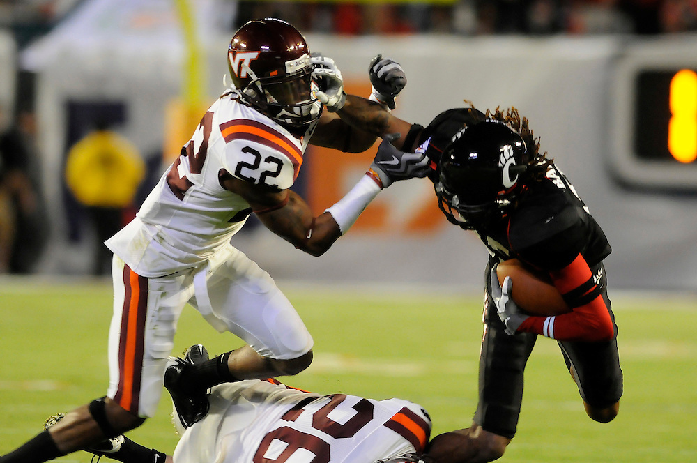 January 1, 2009: Marcus Barnett of the Cincinnati Bearcats is chased by Stephan Virgil and Cody Grimm of the Virginia Tech Hokies during the NCAA football game between the Virginia Tech Hokies and the Cincinnati Bearcats in the Orange Bowl Classic. The Hokies defeated the Bearcats 20-7.