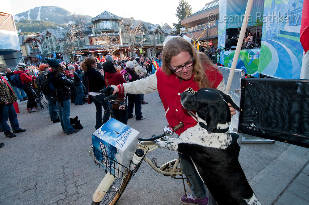 Paul Fornier and his dog Duke show local Canadian spirit by riding a bike with a Flag and a box of Kokanee beer during the 2010 Olympic Winter Games in Whistler, BC Canada