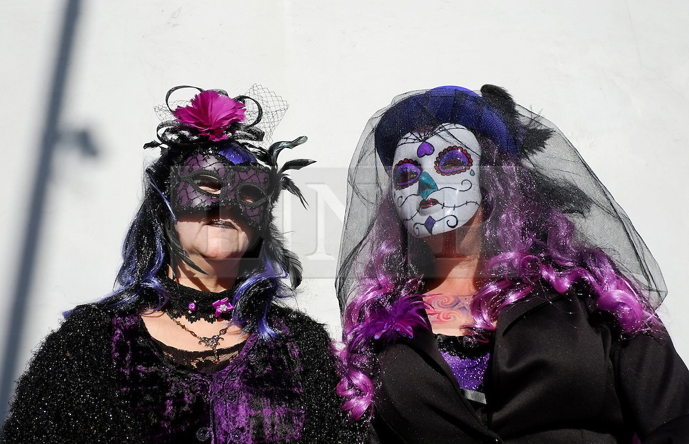 © Licensed to London News Pictures. <br /> 01/11/2014. <br /> <br /> Whitby, Yorkshire, United Kingdom<br /> <br /> Val Ashnorth (L) and Pam Garrod from Grimsby wear masks and extravagant costumes as they attend the 20th anniversary of the Whitby Goth Weekend. <br /> <br /> The event this weekend brings together thousands of extravagantly dressed followers of Victoriana, Steampunk, Cybergoth and Romanticism who all visit the town to take part in celebrating Gothic culture. This weekend marks the 20th anniversary since the event was started by local woman Jo Hampshire.<br /> <br /> Photo credit : Ian Forsyth/LNP
