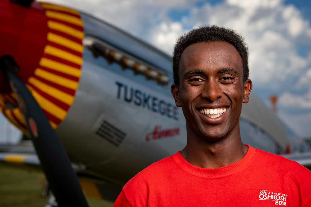 Biya Haile photographed in front of the Tuskegee Airmen P-51 D Mustang, during AirVenture 2019.