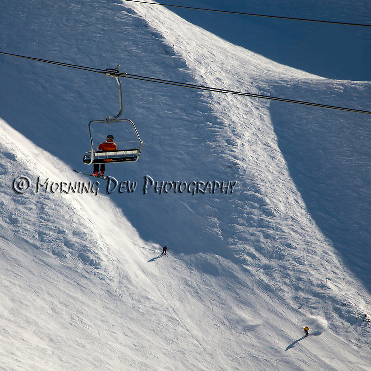 A skier rides up Alyeska's Chair 6 as other people ski the run below.