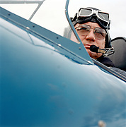 Close up portrait of 60's man in cockpit of vintage plane.
