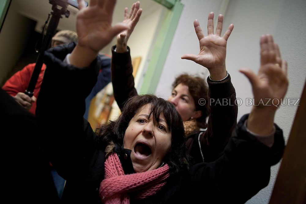 Women stand and shout slogans at the entrance of the local healthcare centre just before it closes at 8pm tonight its emergency hours on January 14, 2013 in Tembleque, near Toledo, Spain. A total of 21 centres, specially in rural areas, in the region of Castilla-La Mancha, are eliminating emergency hours services following budget cuts and privatisations in Spanish health services.
