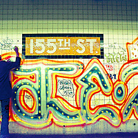 A Graffiti writer tagging using a magic marker. Above another writer's 'Masterpiece'.