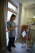Staff nurse Charlotte Howden, inputting data into an iPad on a ward at Whiston Hospital in Merseyside. The device is used to facilitate the Electronic Modified Early Warning System (EMEWS) which helps alert clinical staff to which patients require priority treatment at the hospital. The system, introduced at Whiston Hospital in 2016, allows staff to monitor and regulate patient care in a more efficient way than previous paper-based systems.