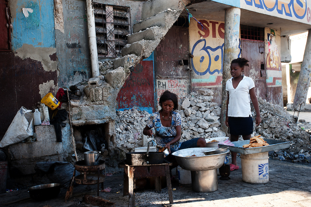 In Delmas 2 area of Port au Prince, a woman cooks food against a backdrop of rubble. Almost 10 months on from the earthquake which struck the city on January 12th, much of the rubble remains on the streets.