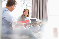Girl with father playing electric guitars at home
