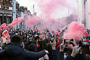 The Liverpool Team bus appears through the smoke on the way to the ground for the Premier League match between Liverpool and Manchester United at Anfield, Liverpool, England on 19 January 2020.
