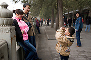 Boy photographs parents at Summer Palace, Beijing. China has a one child family planning policy to limit population.