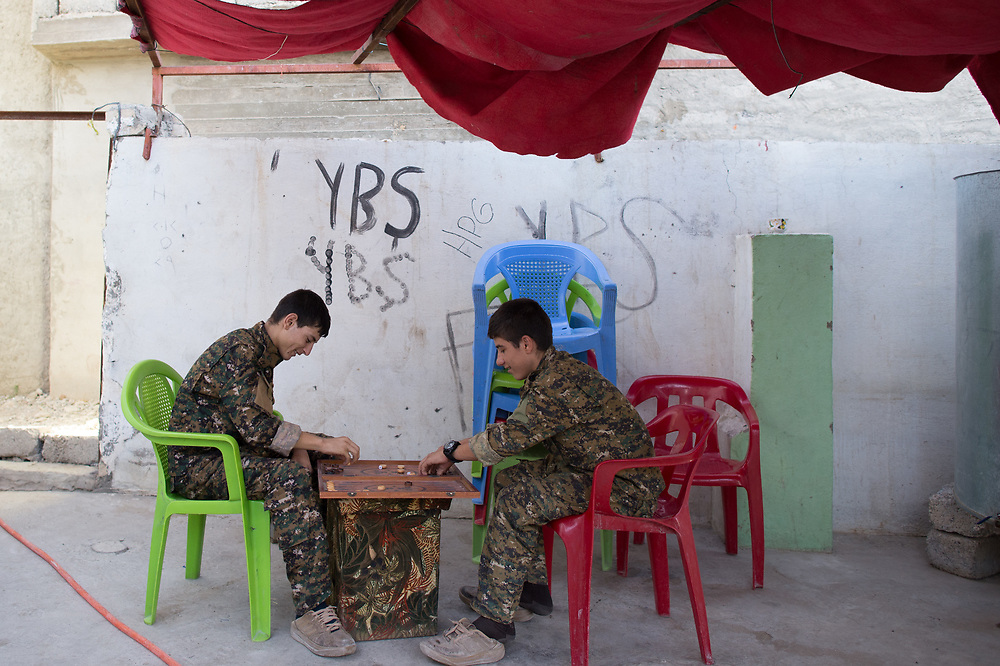 Members of YBS playing backgammon in the courtyard of a military base in Shingal (Sinjar), Iraq, August 26, 2015