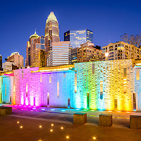 Charlotte at night blue dusk sky photo with Romare Bearden Park colorful water wall and downtown Charlotte buildings. Charlotte is in North Carolina in the Eastern United States.