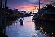 "10 JULY 2011 - AMPHAWA, SAMUT SONGKRAM, THAILAND:   Sunrise on the canal in Amphawa, Thailand, about 90 minutes south of Bangkok. The Thai countryside south of Bangkok is crisscrossed with canals, some large enough to accommodate small commercial boats and small barges, some barely large enough for a small canoe. People who live near the canals use them for everything from domestic water to transportation and fishing. Some, like the canals in Amphawa and nearby Damnoensaduak (also spelled Damnoen Saduak) are also relatively famous for their ""floating markets"" where vendors set up their canoes and boats as floating shops.     PHOTO BY JACK KURTZ"