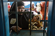 A woman holds her child as she waits for her prescription at the pharmacy counter of the Libreville health center in Man, Cote d'Ivoire on Wednesday July 24, 2013.