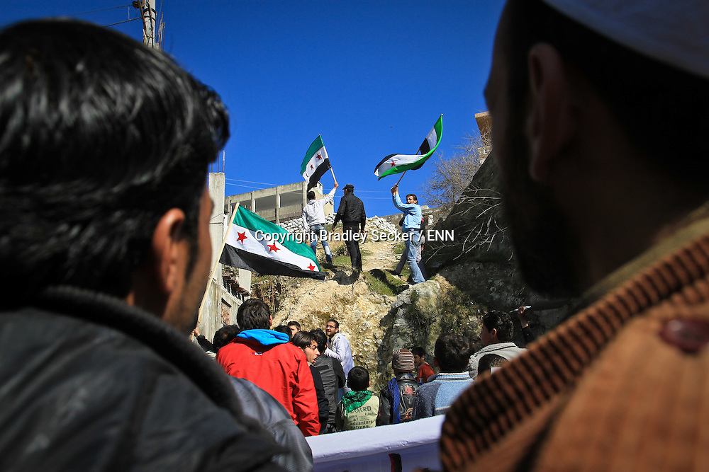 Anti government demonstrators march for regime change beneth a school building being used by the Syrian military for sniper attacks in Al Janoudiyah, Syria.