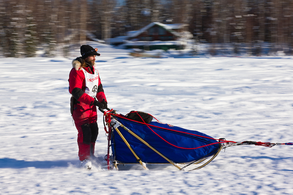 Musher Hank DeBruin competing in the 40th Iditarod Trail Sled Dog Race on Long Lake after leaving the Willow Lake area at the restart in Southcentral Alaska. Afternoon. Winter.