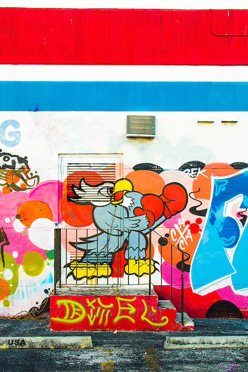 A cartoon-like bird wears boxing gloves in a mural- and graffiti-decorated warehouse wall in Miami's Wynwood arts district