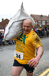 © Licensed to London News Pictures. 28/03/2016. Gawthorpe, UK. An exhausted looking competitor sprints to the finish of the 2016 World Coal Carrying Championships with his 50kg bag of coal. The championships are held annually on Easter Monday in the small West Yorkshire town of Gawthorpe. The competition is a race which involves carrying a 50kg bag of coal up a steep incline to the finish line. Photo credit : Ian Hinchliffe/LNP