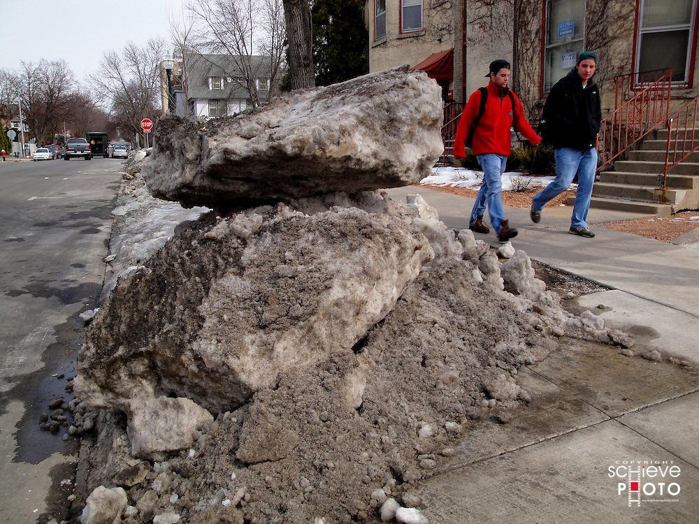 Rocks of snow next to a sidewalk.