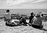 People rest on the beach while waiting for the procession to thanks the St. Bartolomeu celebration. This tradition that dates back to the sixteenth century (1566), and it claims the devil is on the loose during this day. Every year on 24 August  faith and tradition join thousands of people at the feast of St. Bartolomeu do Mar, for ritual that mixes the sacred and the profane.