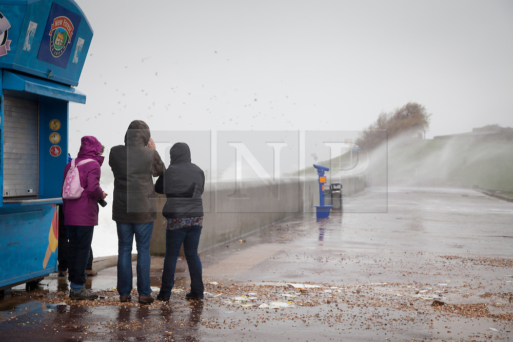 © Licensed to London News Pictures. 01/01/2014. Southsea, UK. A group of people shelter from the weather conditions as strong winds hit the coast of Southsea, Hampshire, UK on New Years Day 2014. Photo credit : Rob Arnold/LNP