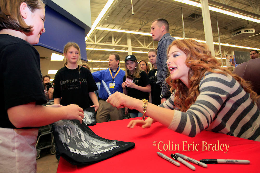 Twilight star Rachelle Lefevre, right, who plays character Victoria, signs autographs for fans at the Walmart store in Riverton, Utah during the midnight DVD movie release event March 21, 2009. (AP Photo/Colin Braley)