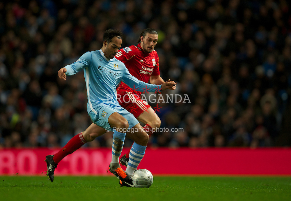 MANCHESTER, ENGLAND - Wednesday, January 11, 2012: Liverpool's Andy Carroll in action against Manchester City's Joleon Lescott during the Football League Cup Semi-Final 1st Leg at the City of Manchester Stadium. (Pic by David Rawcliffe/Propaganda)