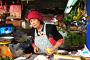 An elderly woman looks out from her fruit stand at a local market in the northern Thailand town of Chiang Mai.