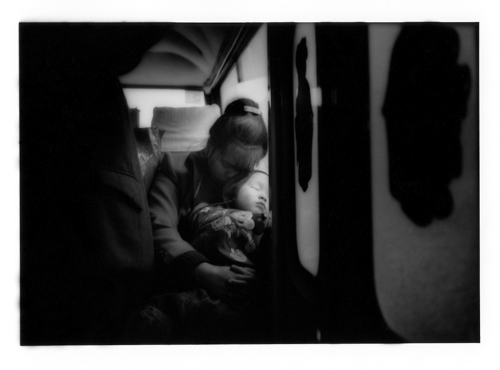 Mother cradles her sleeping child on a bus. Near Guilin, Guangxi, China.  1998