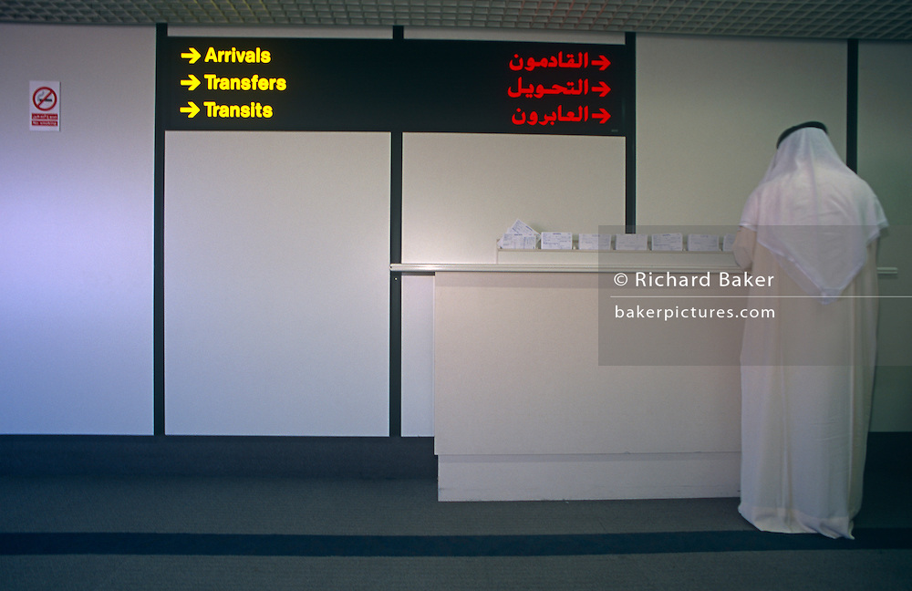 An arab gentleman fills out arrivals paperwork after an arrived flight to the Gulf state of Bahrain's international airport.