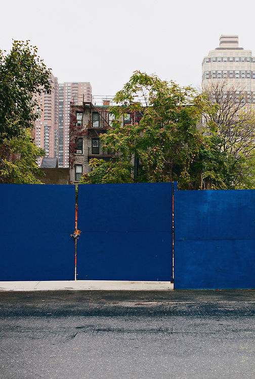 Blue plywood fence in front of old apartment building on construction site, Hells Kitchen, New York, New York, US