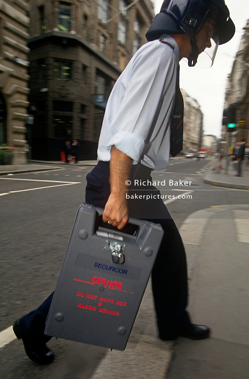 A Securicor guard delivers a cash box to a City of London bank. Walking quickly to avoid delays in the street, the employee of this security company carries the secure box wearing protective helmet in case of an armed robbery - his most vulnerable body area being the head and neck. The box is padlocked and contains explosive dyes and loud alarms if forcefull opened. Securicor was originally founded by Edward Shortt, a former Liberal Cabinet Minister, in 1935 as Nightwatch Services: its guards rode bicycles and wore old police uniforms. However in 1939 it was taken over by Lord Willingdon and Henry Tiarks who developed it into a leading security business. It changed its name to Security Corps in 1951 then shortened to Securicor in 1953.