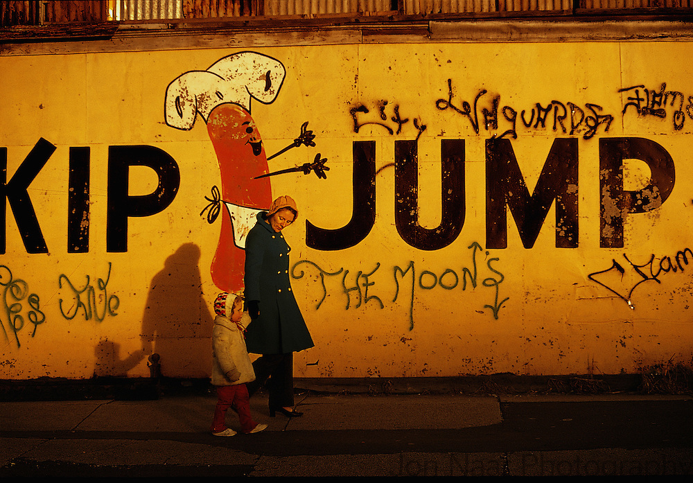 Mother and child walking with Kip Jump sign and graffiti including: City Vanguards and The Moons.  Coney Island.  1973   Taken with a Leica M4 on Kodachrome film. First published in Birth of Graffiti (2005).