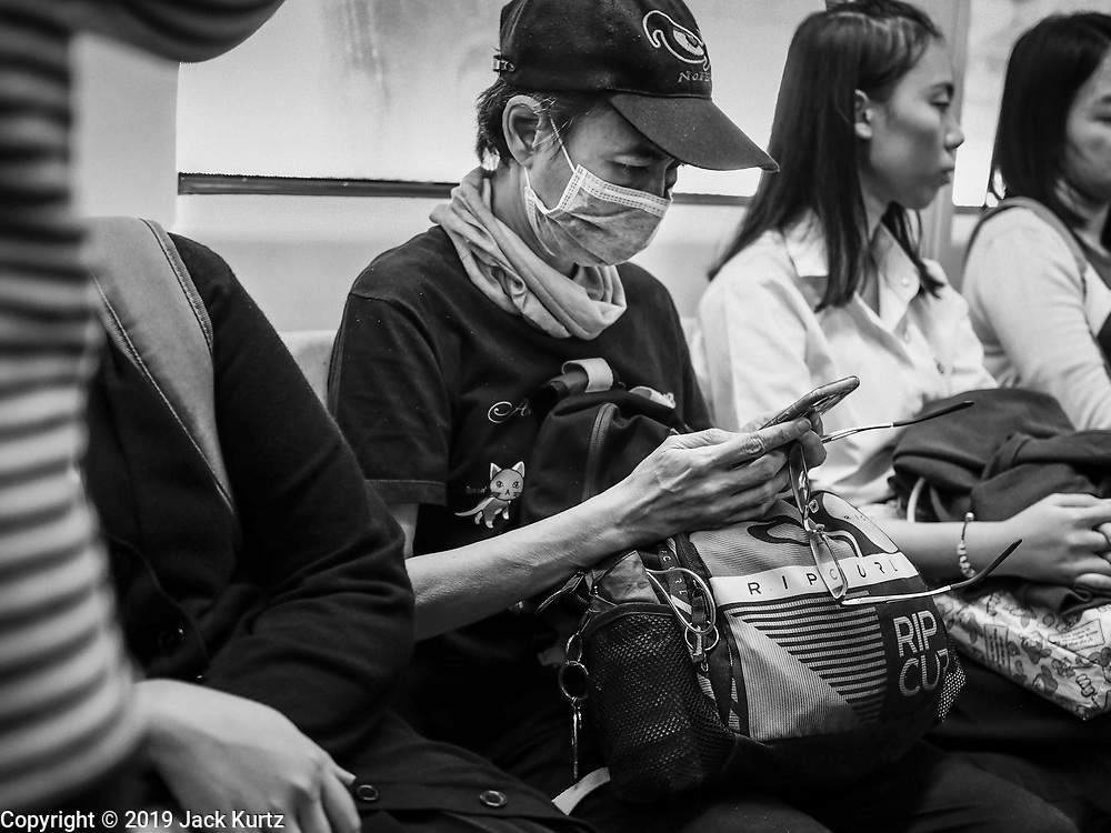 "14 JANUARY 2019 - BANGKOK, THAILAND:    A woman wearing a dust filter on the skytrain in Bangkok. Bangkok has been blanketed by heavily polluted air for almost a week. Monday morning, the AQI (Air Quality Index) for Bangkok  was 182, worse than New Delhi, Jakarta, or Beijing. The Saphan Kwai neighborhood of Bangkok recorded an AQI of 370 and the Lat Yao neighborhood recorded an AQI of 403. An AQI above 50 is considered unsafe. Public health officials have warned people to avoid ""unnecessary"" outdoor activities and wear breathing masks to filter out the dust.    PHOTO BY JACK KURTZ"