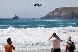 © Licensed to London News Pictures. 20/05/2020. Padstow, UK. Onlookers watch as HM Coastguard Search and Rescue helicopter performs a training exercise at Constantine Bay on the north coast of Cornwall during hot weather. The weather in the south-west is forecast to be warm for the following week. Photo credit : Tom Nicholson/LNP