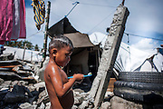 A kid prepares to brush his teeth at barangay 88 on June 11 2014 in Tacloban, Philippines. Tacloban city and the surrounding villages were devastated after typhoon Hayan passed over leaving at least 6,200 people dead and a high number of disappeared on November 8, 2013.
