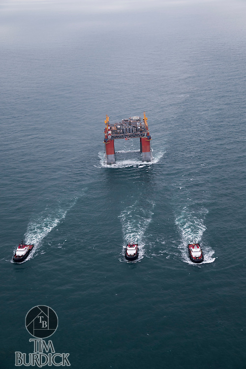 "Deepwater offshore oil platform ""DELTA HOUSE"" being towed offshore from Kiewit in Ingleside, Texas by Crowley Maritime Corporation's OCEAN CLASS Tugs. (Aerial Photography by Tim Burdick)"